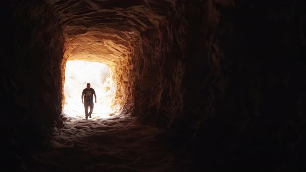 View of man walking into tunnel into the darkness Royalty-free stock video