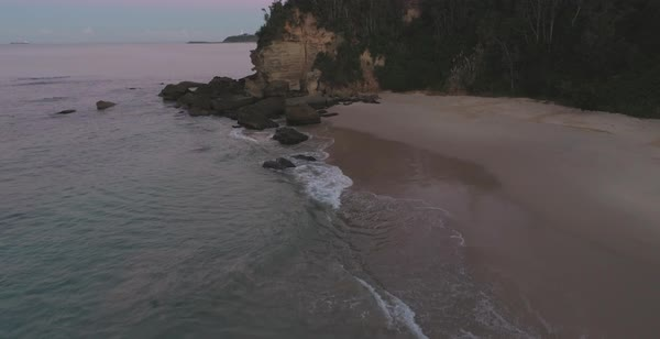 Norah Head aerial view showing sandy beach, rocky cliff, thick foliage with lighthouse peeking in the distance Royalty-free stock video