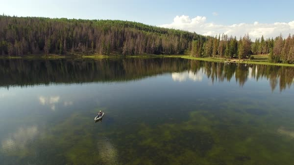 Aerial view rotating around woman fishing in kayak in glassy lake. Royalty-free stock video