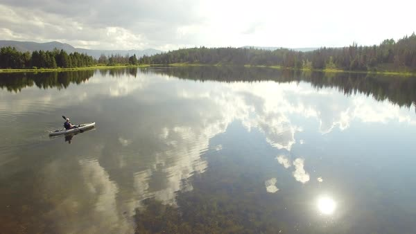 Sky reflecting in glassy lake as woman paddles kayak to go fishing. Royalty-free stock video