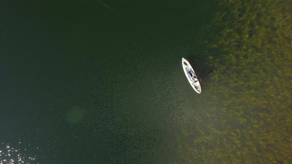 Rising top down view of woman fishing in kayak viewing the depths of the lake. Royalty-free stock video