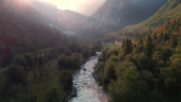 Aerial view of the sun shining through the mist over Lepena Valley flying upstream viewing the Soca river flowing out of the canyon. Royalty-free stock video