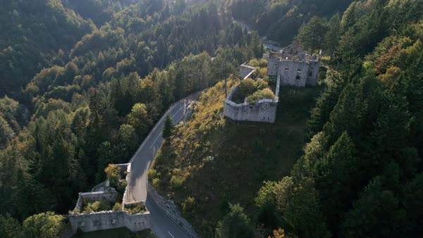 Aerial view flying over Trdnjava Predel, Predel Fortress sitting on hilltop in thick pine tree forest as road winds around. Royalty-free stock video