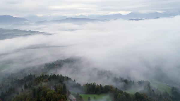 Aerial view of low fog moving through the forest across the landscape revealing a farm house in Skofja Loka Slovenia Royalty-free stock video