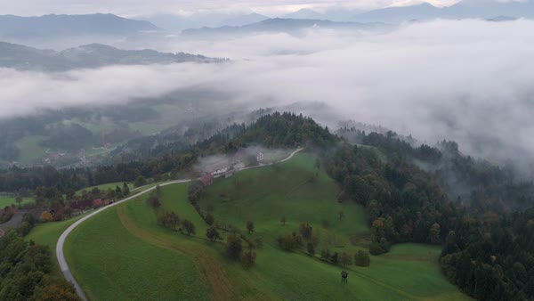 Aerial view of road leading towards farmhouse in foggy forest landscape in Skofja Loka Slovenia. Royalty-free stock video