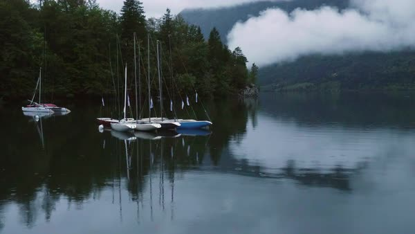 Sailboats on Lake Bohinj on dreary day as light rain sprinkles on the waters surface. Royalty-free stock video