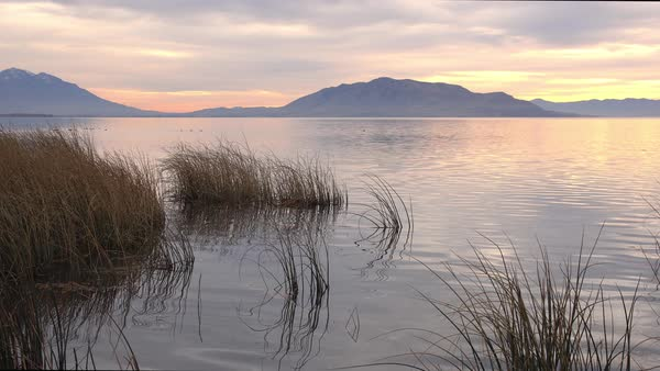 View of Utah Lake in the evening as the sun is setting and the water reflects the glow from the color in the clouds above. Royalty-free stock video