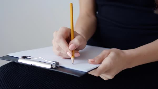 Close-up of a female hand writing on an blank notebook with a yellow pencil Royalty-free stock video
