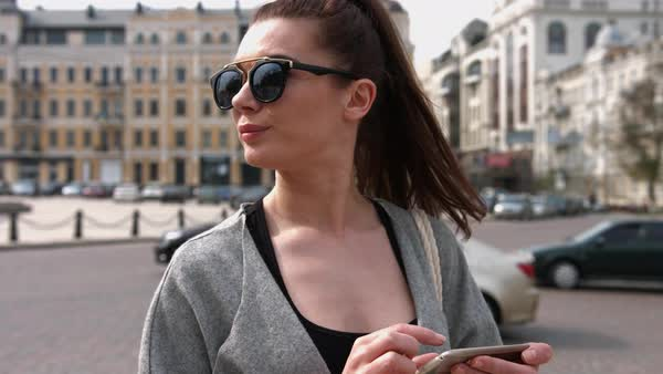 Brunette woman using gps navigation on the smart phone while strolling on the street Royalty-free stock video