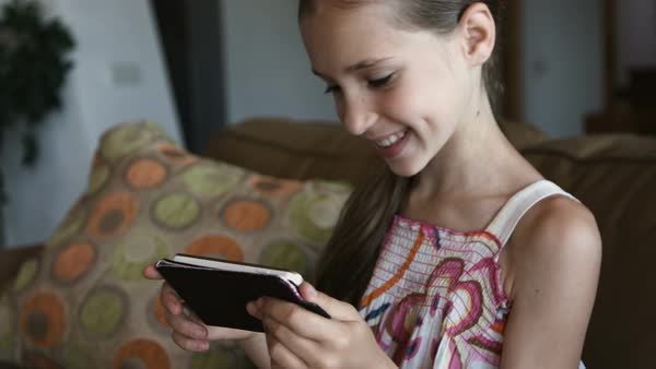 Cute smiling little girl using modern smartphone in living room, close-up Royalty-free stock video