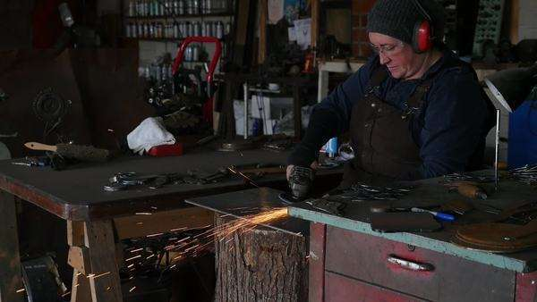 Medium shot of a blacksmith polishing a piece of metal with an angle grinder Royalty-free stock video