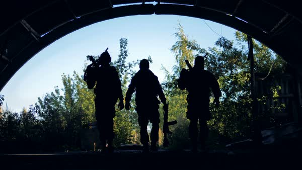 Three silhouettes of armed soldiers moving to the camera Royalty-free stock video