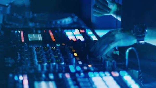 A DJ behind the console, on stage, mixing tracks in atmospheric dance party strobing and flashing lights. Royalty-free stock video