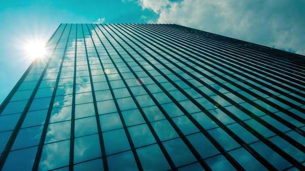 Beautiful thick white summer clouds and sun with occasional rays reflected on the surface of a big corporate building/skyscraper, timelapse Royalty-free stock video