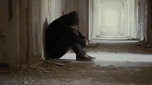 Hooded young man inside destroyed abandoned building sitting back to the wall Royalty-free stock video