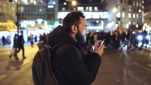 A  young man is browsing his cellphone on a busy urban street at night. Royalty-free stock video