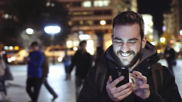 A smiling cheerful young man is using his cellphone at night  walking in a European city landmark  Royalty-free stock video