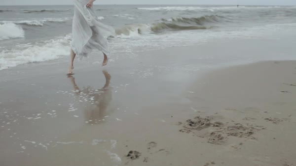 Medium wide shot of a woman hopping on a sandy beach Royalty-free stock video