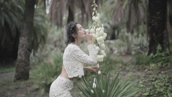Medium shot of a woman smelling a white flower in a garden Royalty-free stock video
