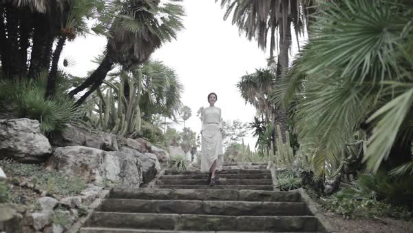 Wide shot of a woman walking down on stairs in a garden Royalty-free stock video