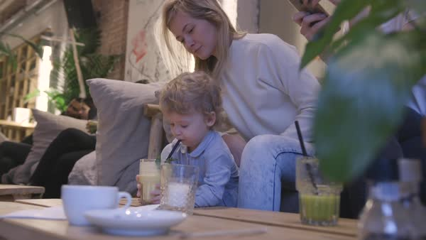 Hand-held shot of a mother helping her toddler drink through a straw Royalty-free stock video