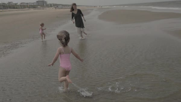 Hand-held shot of a young mother running with her children on a beach Royalty-free stock video