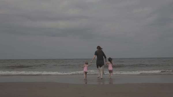 Hand-held shot of a young mother running with her children into sea Royalty-free stock video