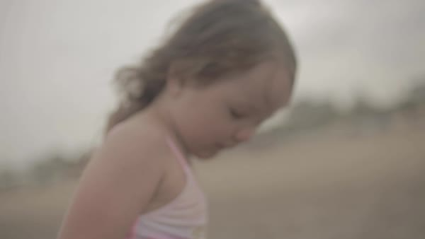Hand-held shot of a girl standing on a beach and looking down Royalty-free stock video