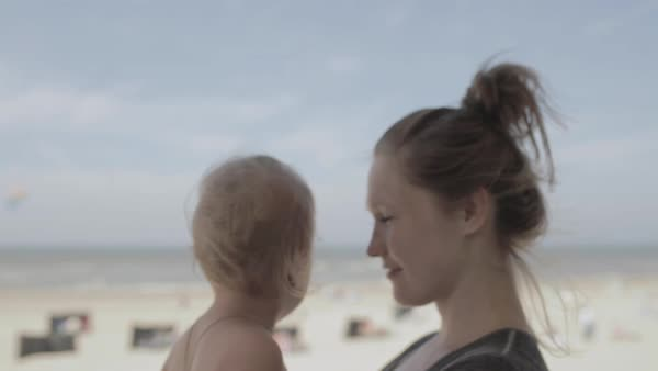 Hand-held shot of a young mother holding her child on a beach Royalty-free stock video