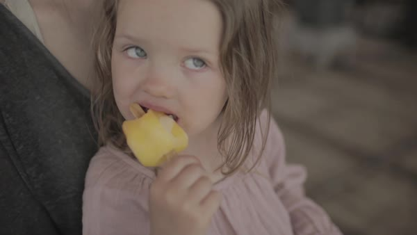 Hand-held shot of a girl eating a popsicle on lap of her mother Royalty-free stock video