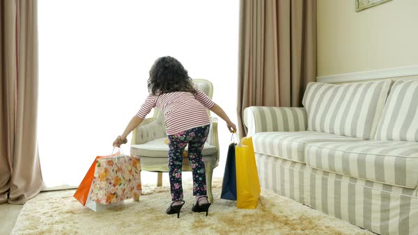 e1668c7bafe Cute little girl on high heels and with shopping bags imitating her mother  Royalty-free