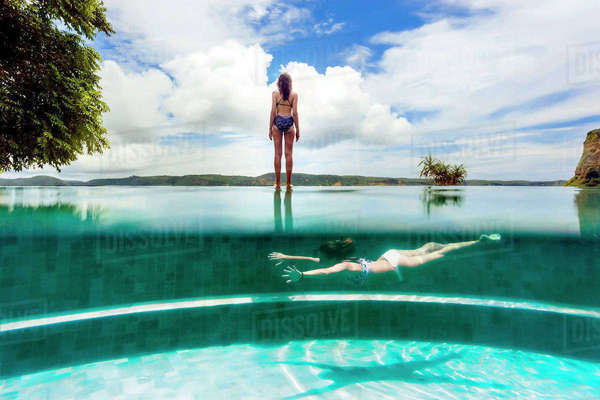 Young woman swimming in outdoor swimming pool beside woman standing outside stock photo dissolve for Female only swimming pool london