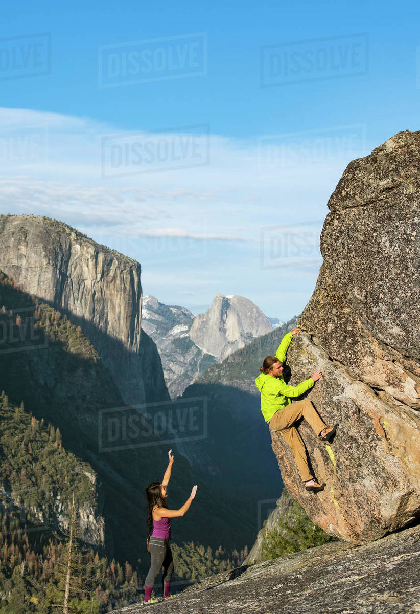 climbers bouldering on rock in yosemite with half dome and el