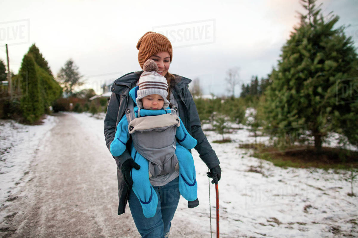 Mother Walking With Baby In Carrier At Christmas Tree Farm Langley British Columbia Canada Stock Photo