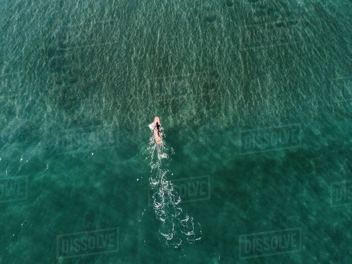 Aerial View Of Female Surfer Surfing In Crystal Clear Water