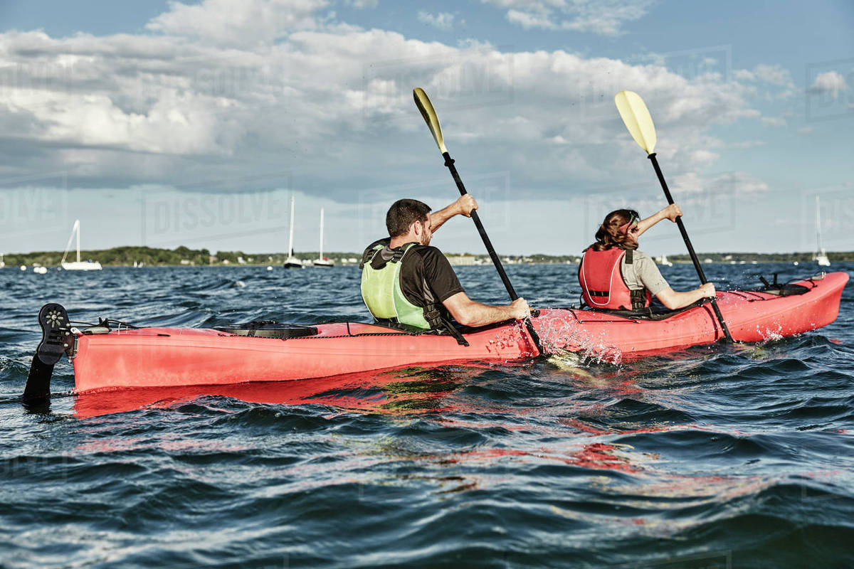 Couple Using Teamwork While Paddling In Tandem Sea Kayak Portland Maine USA