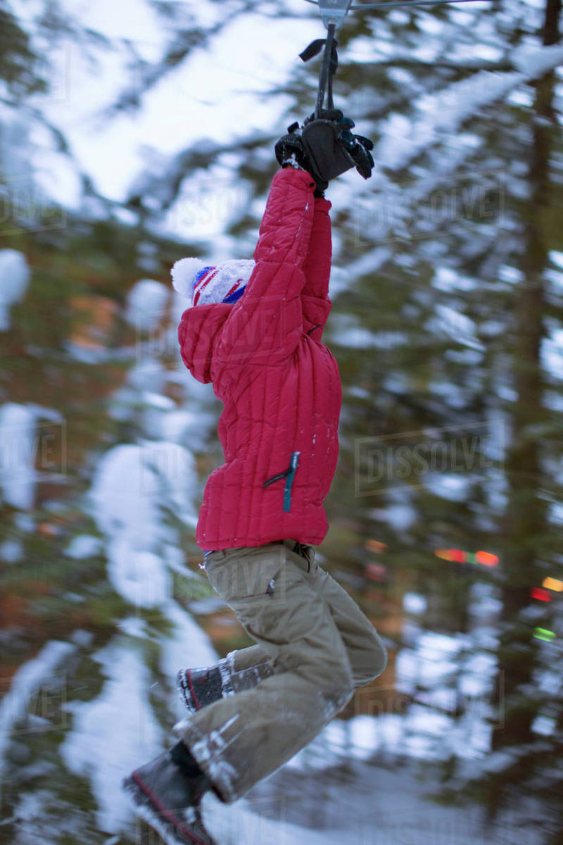 Young boy ziplining against snow-covered trees on homemade zipline, Sandpoint, Idaho, USA