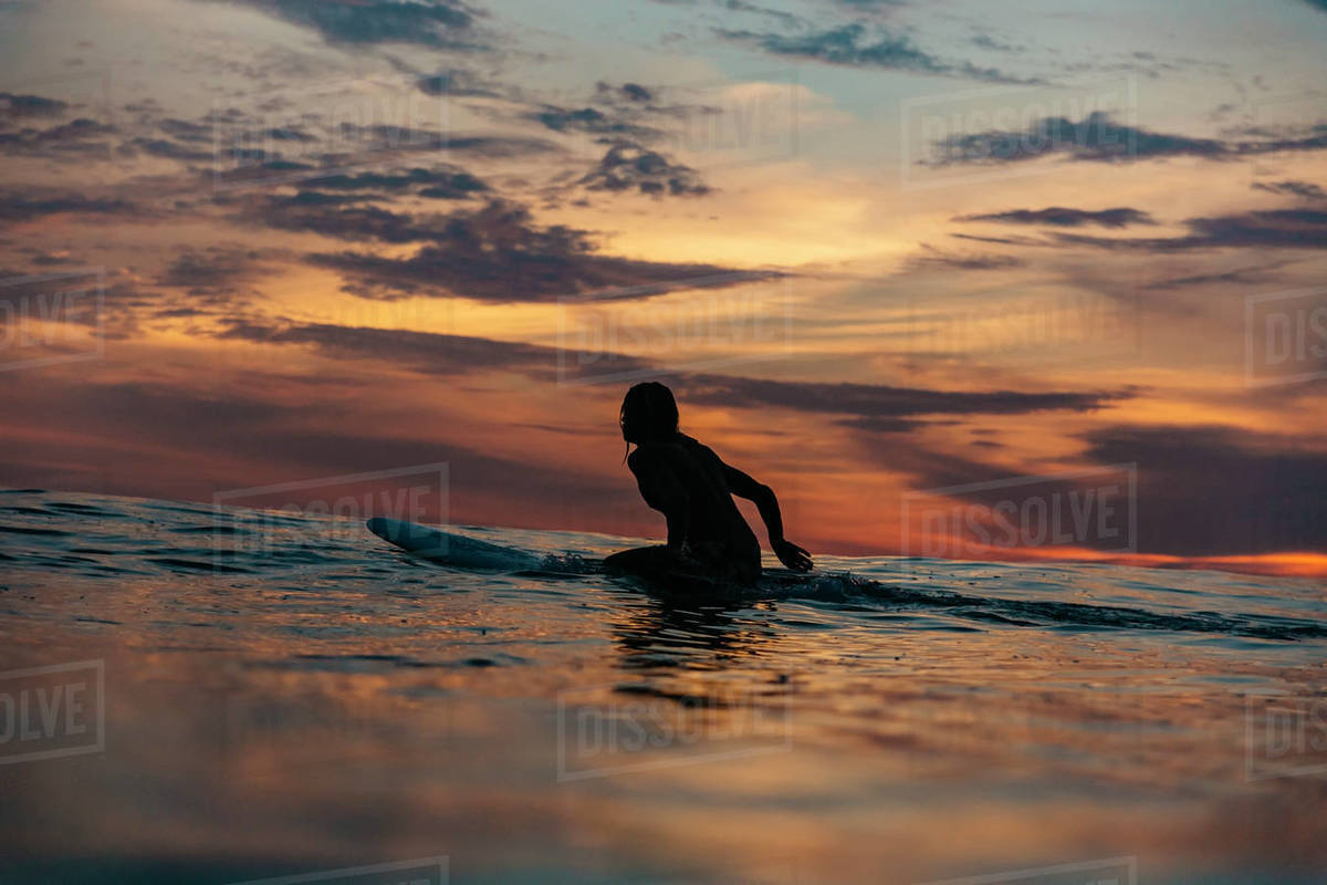 73bad71e72 Surfer in sea at sunset