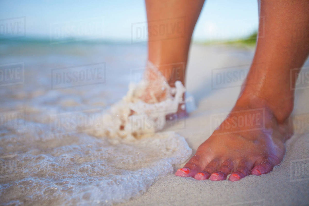 Surf Washes Over A Young Womans Feet At A Beach In Cayo Coco Cuba