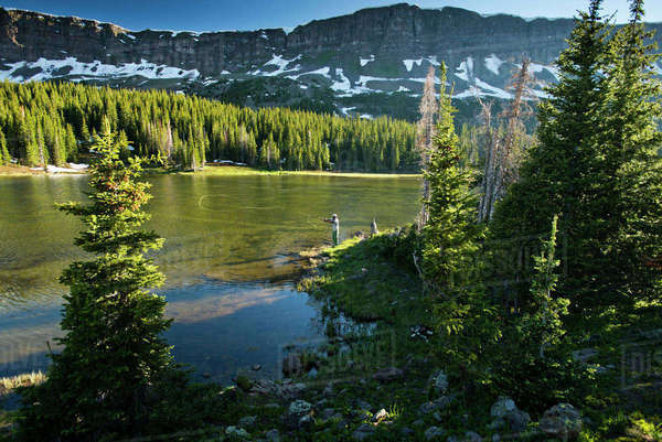 A fly fisherman fishes a high alpine lake.  Royalty-free stock photo