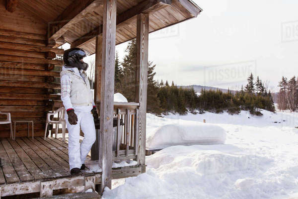 Female snowmobiler on porch at log cabin Royalty-free stock photo