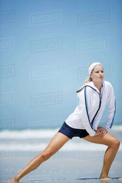 Young woman on beach, stretching Royalty-free stock photo