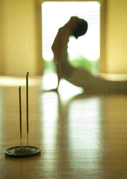 Woman doing cobra pose, side view, focus on incense in foreground Royalty-free stock photo