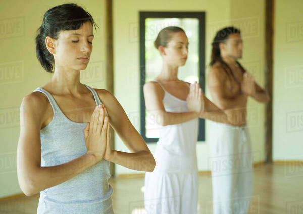 Yoga class standing in prayer position Royalty-free stock photo