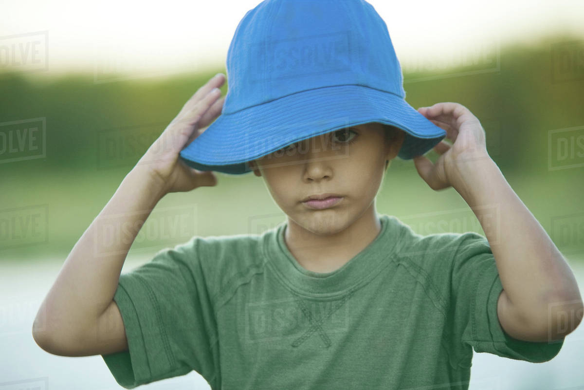 Boy putting on hat, head and shoulders Royalty-free stock photo