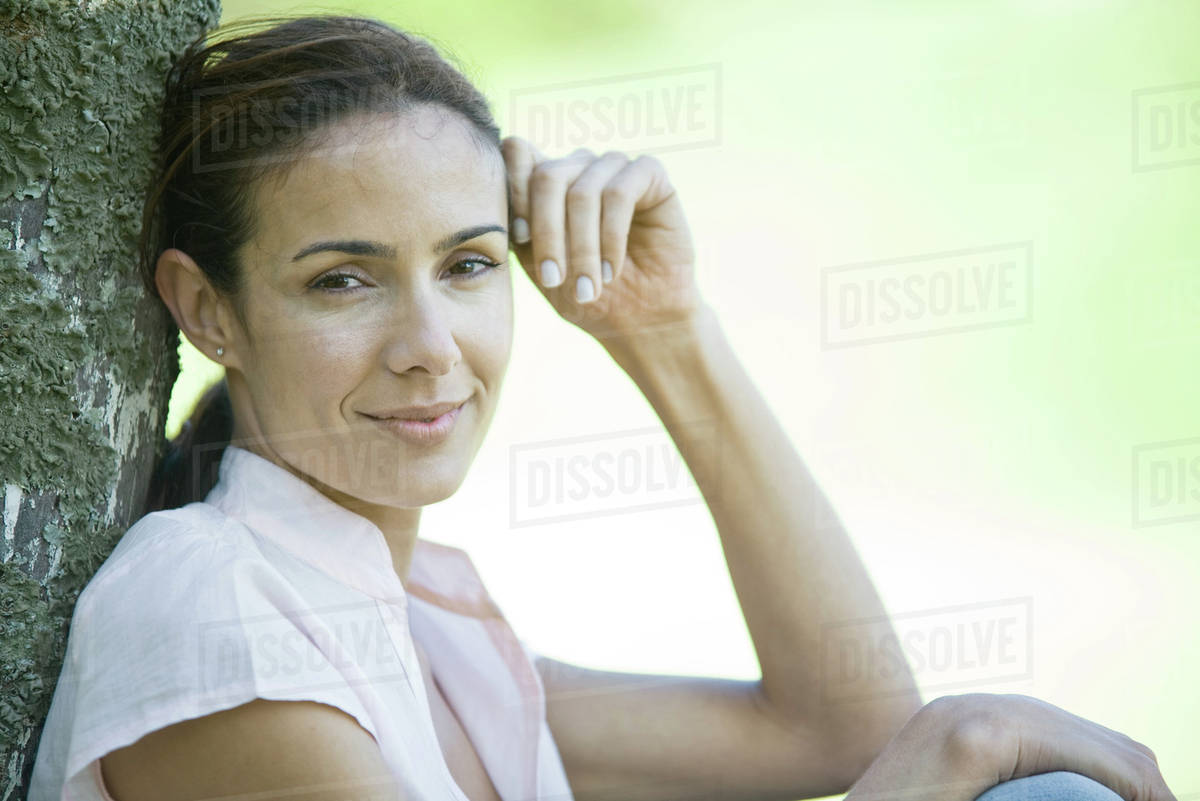 Woman leaning against wooden post, looking at camera, head and shoulders Royalty-free stock photo