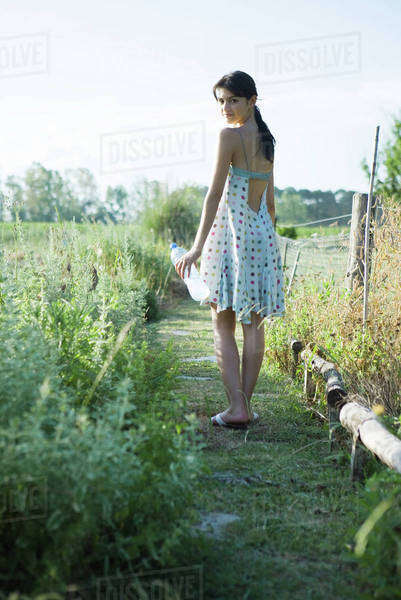 Young woman standing in garden with bottle of water, looking over shoulder at camera Royalty-free stock photo