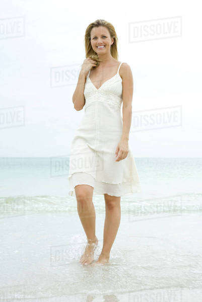Woman in sundress walking in surf, hand in hair, smiling at camera Royalty-free stock photo