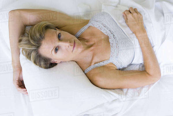 Woman lying on pillow, smiling at camera Royalty-free stock photo