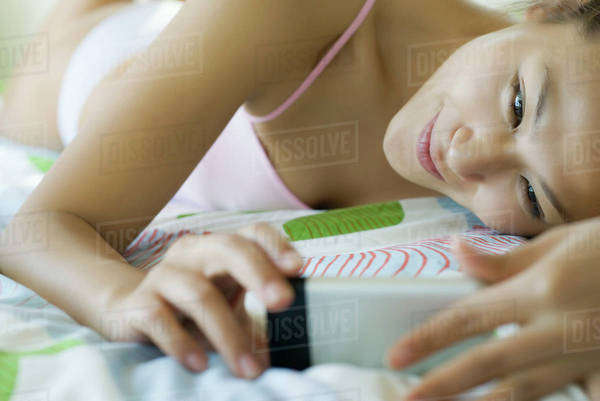 Smiling young woman lying on bed looking at cell phone Royalty-free stock photo